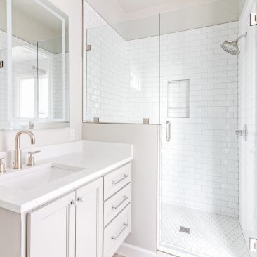 Bathroom Remodel with white hex tiled shower floor and subway tile, gray cabinets