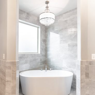 Master Bathroom Home Remodel with freestanding bathtub and chandelier