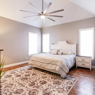Master Bedroom Home Remodel with wood floors and oversized ceiling fan