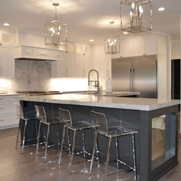 Kitchen renovation with gray and white painted cabinets and metal bar stools
