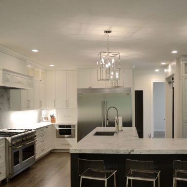 Gray island, white cabinets, pendant lighting, stainless steel appliances