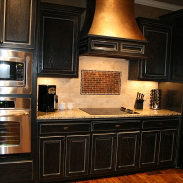 Kitchen with black cabinets and hood, stainless steel appliances