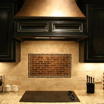 Kitchen with black cabinets and hood