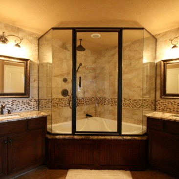 Bathroom with glass enclosed shower and dual vanities