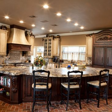 French Country kitchen with two tone cabinets, island, brushed granite, brick floor.