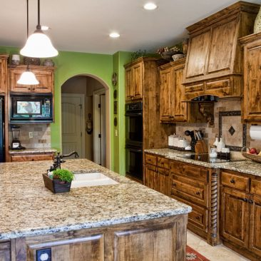 Kitchen with large island, stained cabinets, green walls