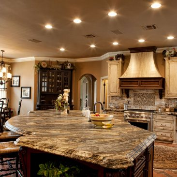 French Country kitchen. 2 tone cabinets, huge island, brushed grainte for a leather look, brick floor.