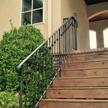Garage breezeway wood steps with metal railing.