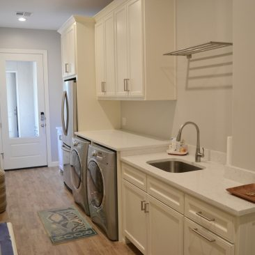 Laundry Room or mudroom addition with drying rack, cabinets, refrigerator