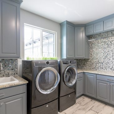 Custom Laundry Room with bubble backsplash, painted cabinets, distressed wood tile floor