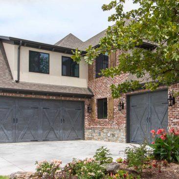 New Custom Home - Hand Rubbed gray garage doors, brick, stone & stucco