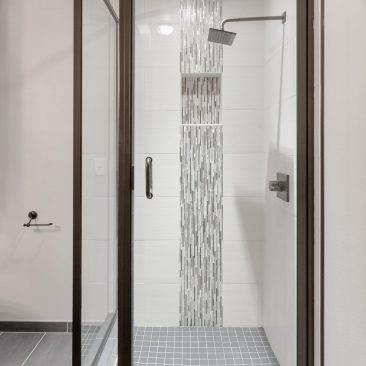 Custom shower with vertical stripe glass tile accent