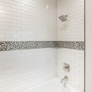 Custom Shower with glass subway tile & modern showered