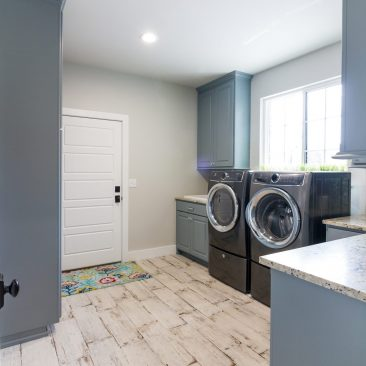 New Construction Laundry Room with wood tile & blue cabinets